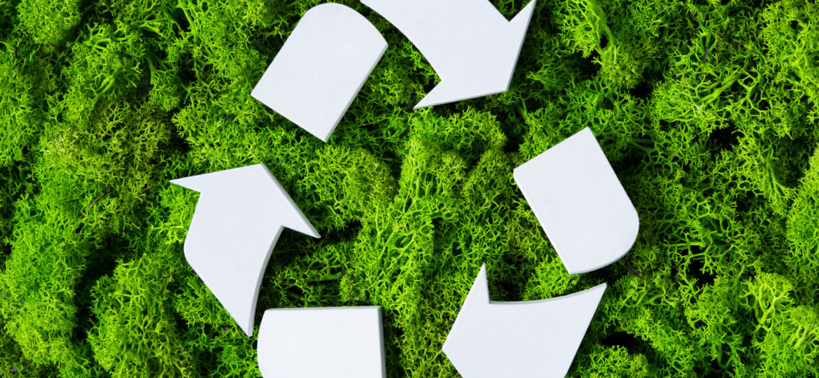Top view of white recycle eco symbol on green moss with copy spa